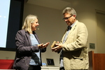 Professor of English Paul Harris, right, receives a migrating stone from poet Alyson Hallett, left
